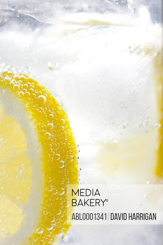 Extreme close up of a slice of lemon floating in sparkling iced water