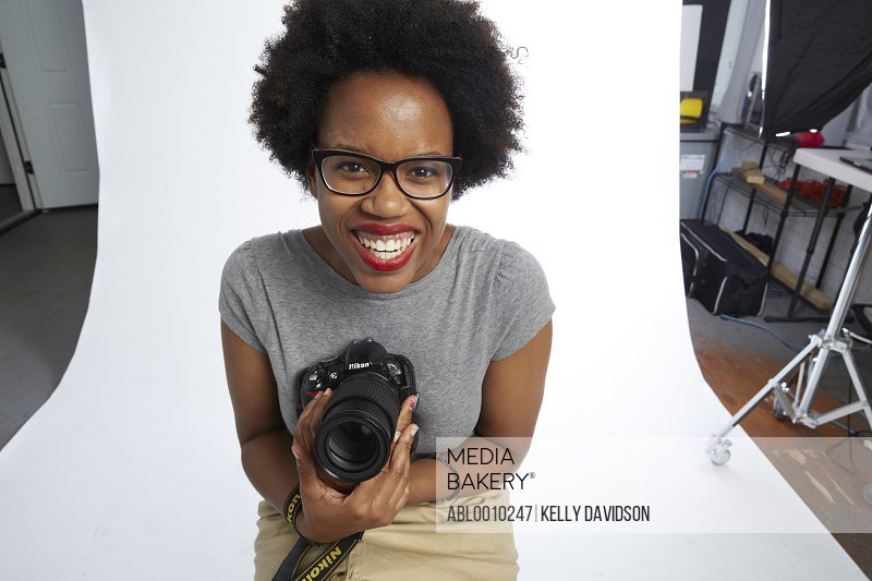 Female Photographer Holding Camera Smiling