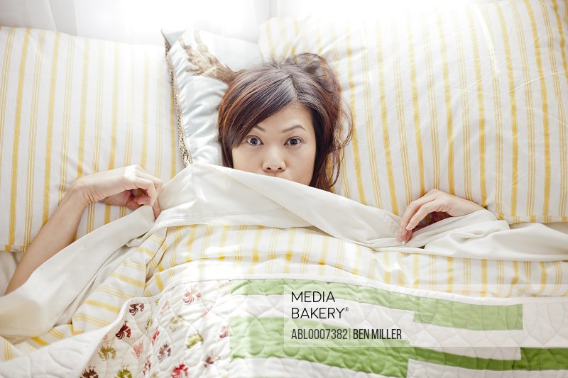 Woman in Bed Peering out from Under Bed sheet