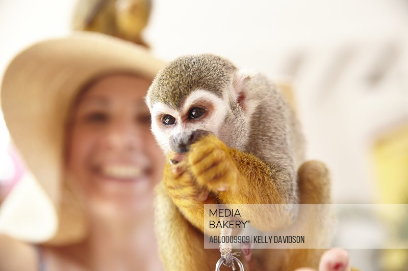 Woman Holding Spider Monkey Smiling