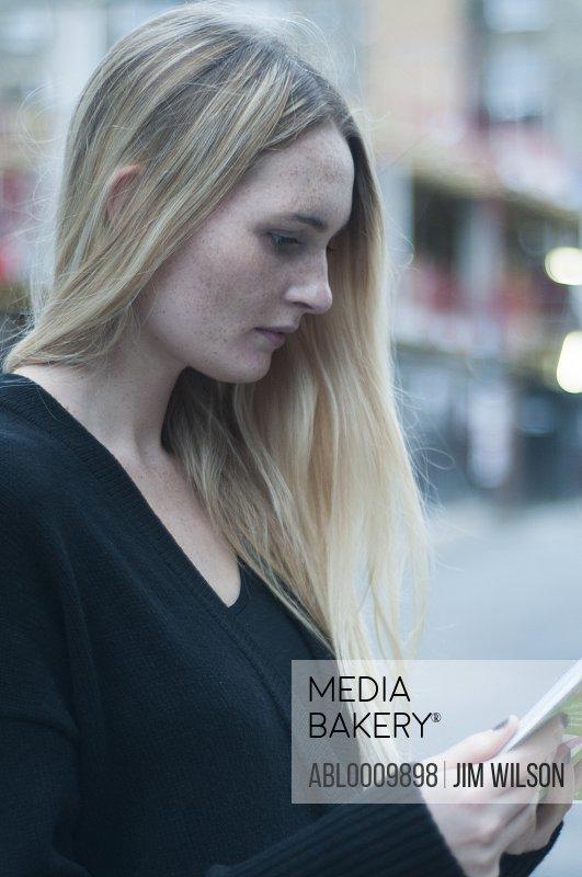 Woman Reading Guidebook in Street