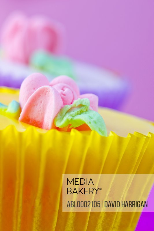 Bright Yellow Cupcake with Pastel Pink Flower Decoration