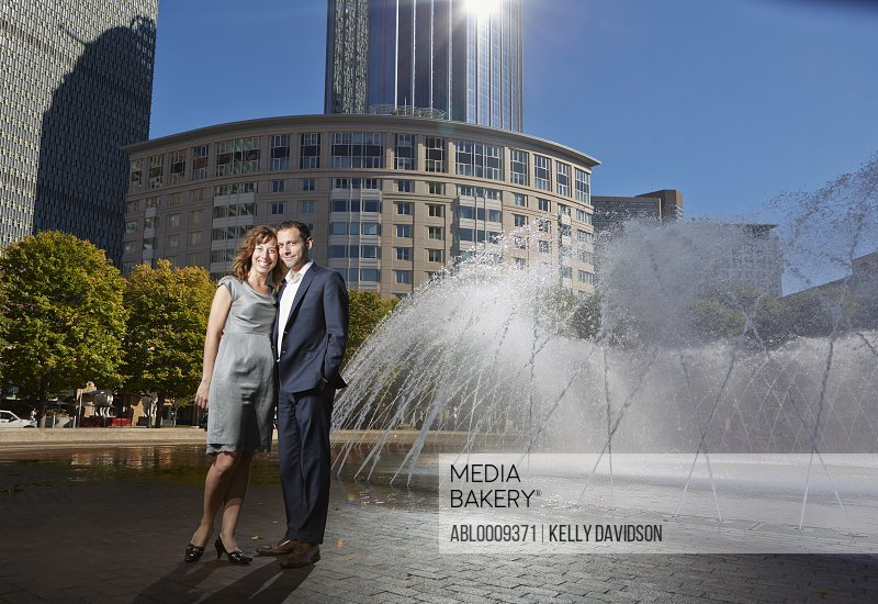 Smiling Couple Standing by Fountain