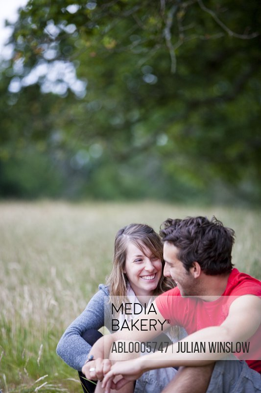Close up of a smiling couple sitting under a tree in a field