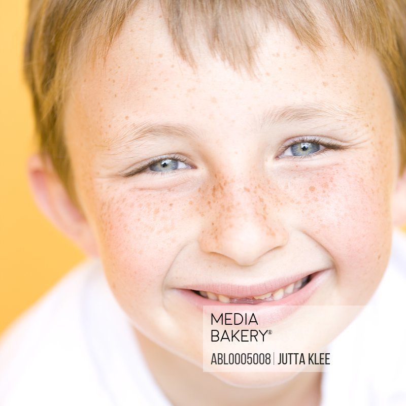 Close up of a smiling young boy with missing tooth