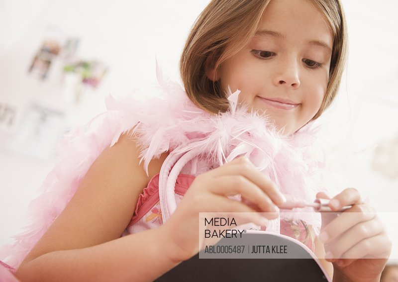 Girl wearing a pink feather boa holding a lip-gloss