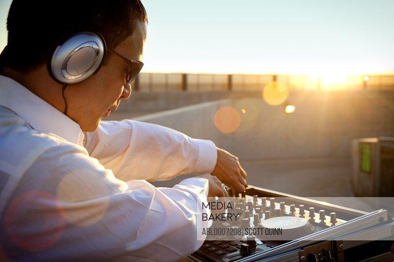 DJ Using Mixing Console at Sunrise