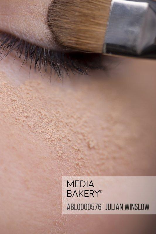 Woman applying eye make-up with eyeshadow brush and makeup powder under eye