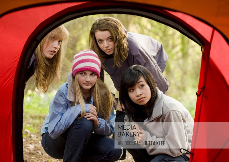 Teenage girls at campsite crouching in front of tent entrance looking in with curiosity