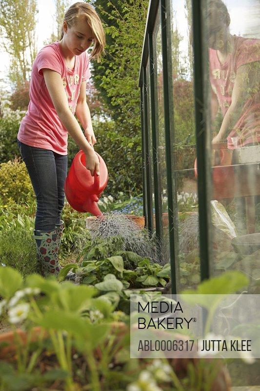 Teenage girl watering plants in a garden