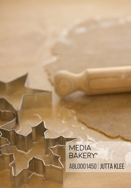 Close up of rolled out pastry dough with wooden rolling pin and cookie cutters