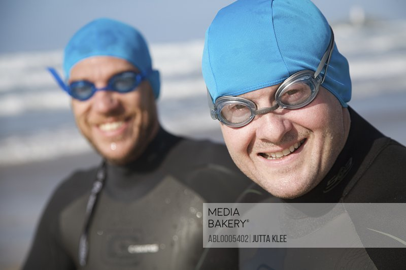 Two men wearing bathing caps and goggles smiling