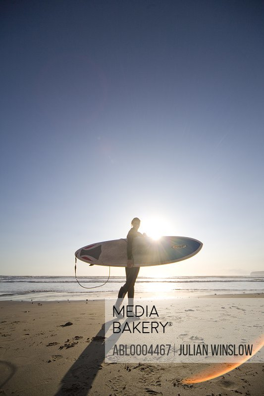 Young woman surfer walking on a beach with surfboard