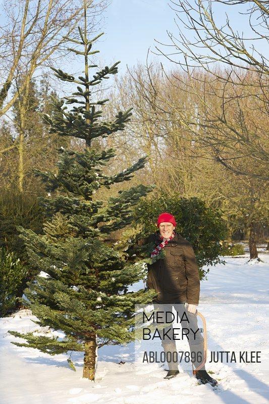 Man Holding Christmas Tree and Handsaw