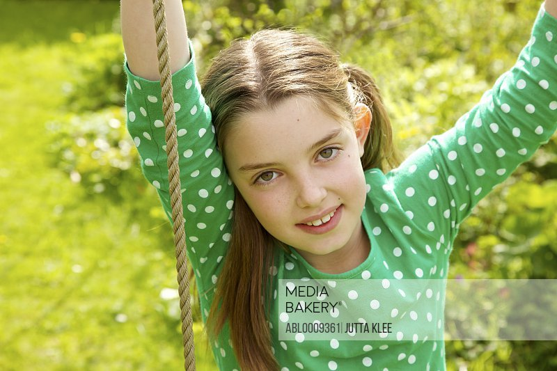 Young Girl Sitting on Swing, Close-up View