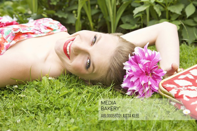 Smiling young woman lying on the grass with a flower in her hair