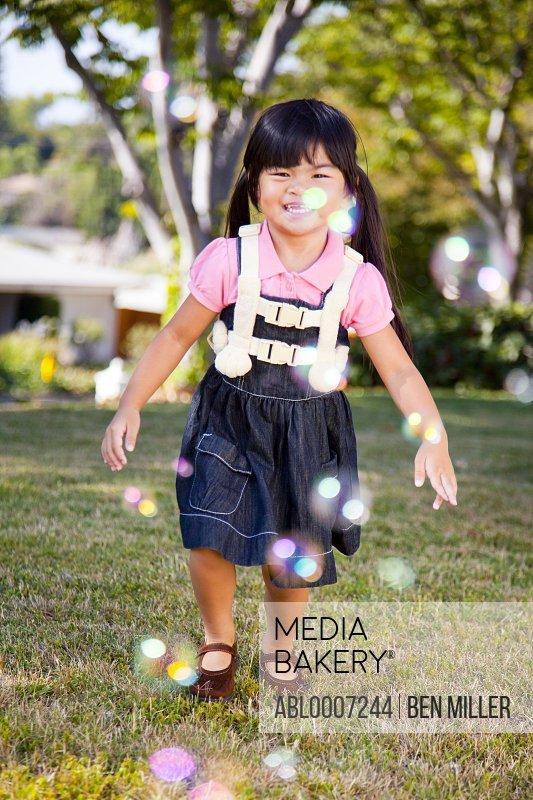 Smiling Young Girl Walking in Garden