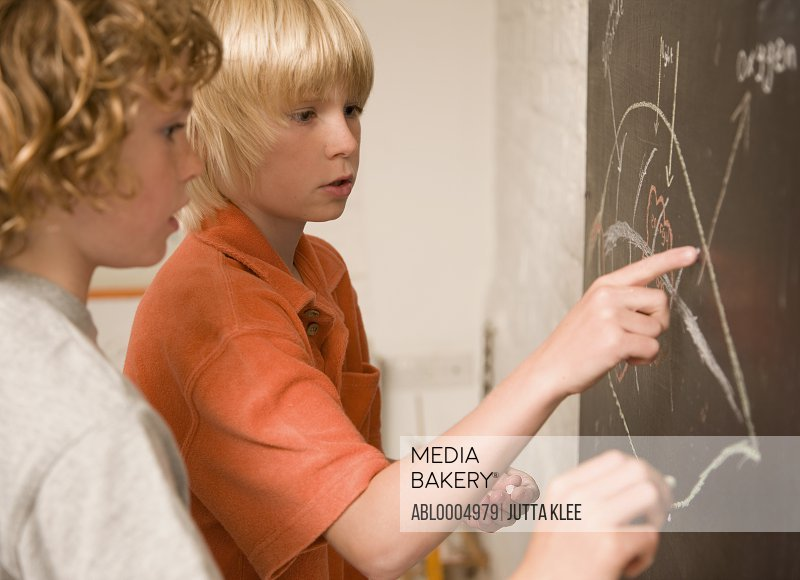 Two young boys writing on a blackboard