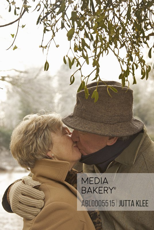 Mature couple standing under a tree kissing