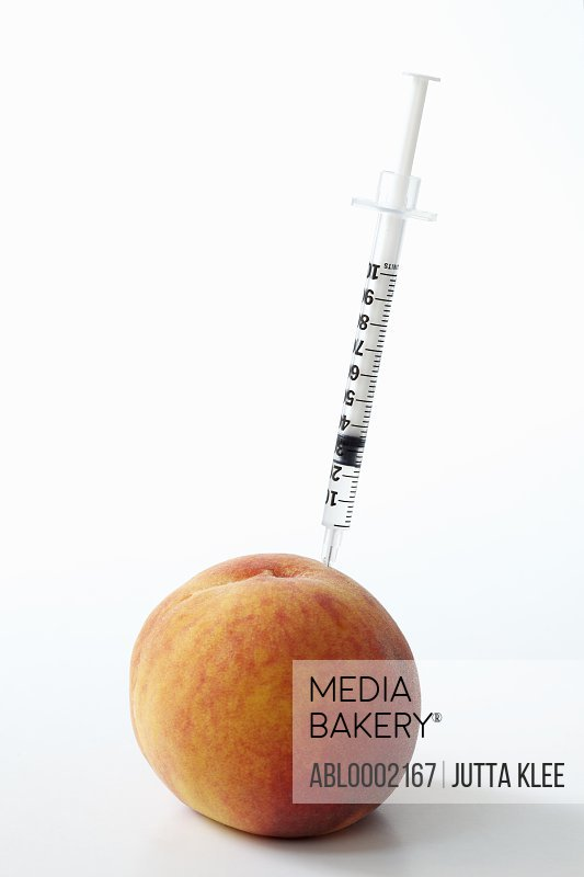 Hypodermic Needle Inserted in a Peach