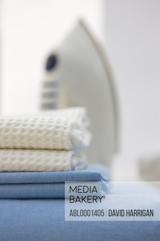 Close up of a stack of bed linen and an iron