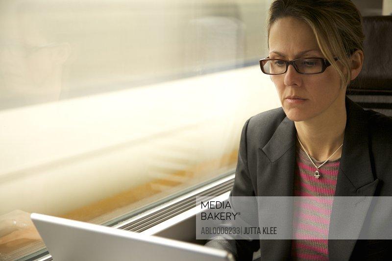 Woman on train using laptop computer