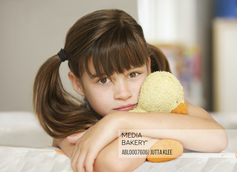 Girl Hugging a Stuffed Toy Duck