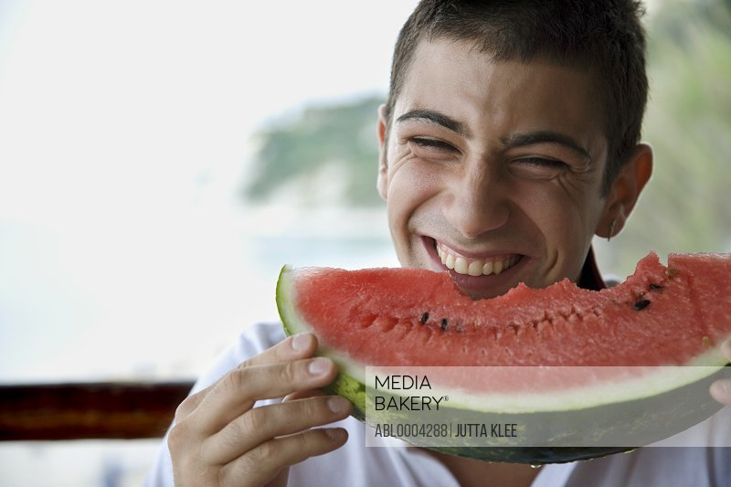 Young man eating water melon and laughing