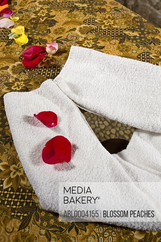 Folded Towel and Petals on Massage Table