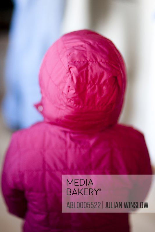 Back view of a little girl wearing a red hooded parka