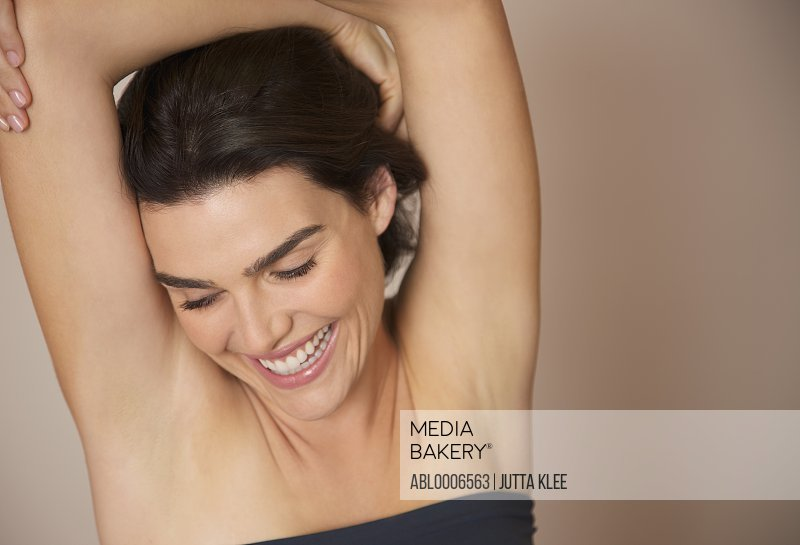 Smiling Woman with Arms Crossed above Head - Close-up view