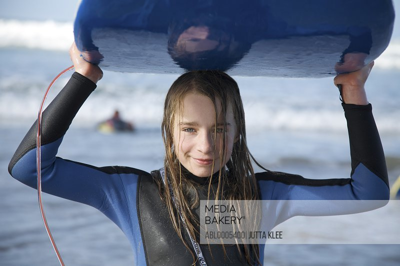 Smiling and wet girl holding a surfboard on her head coming out of the sea
