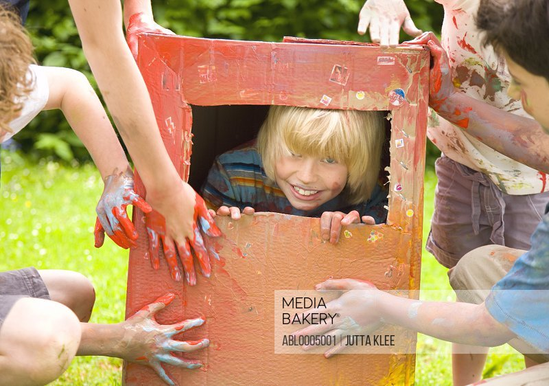 Young blonde boy trapped  in a cardboard box playing with friends