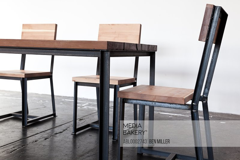 Iron Frame Wooden Table and Chairs on Concrete Floor