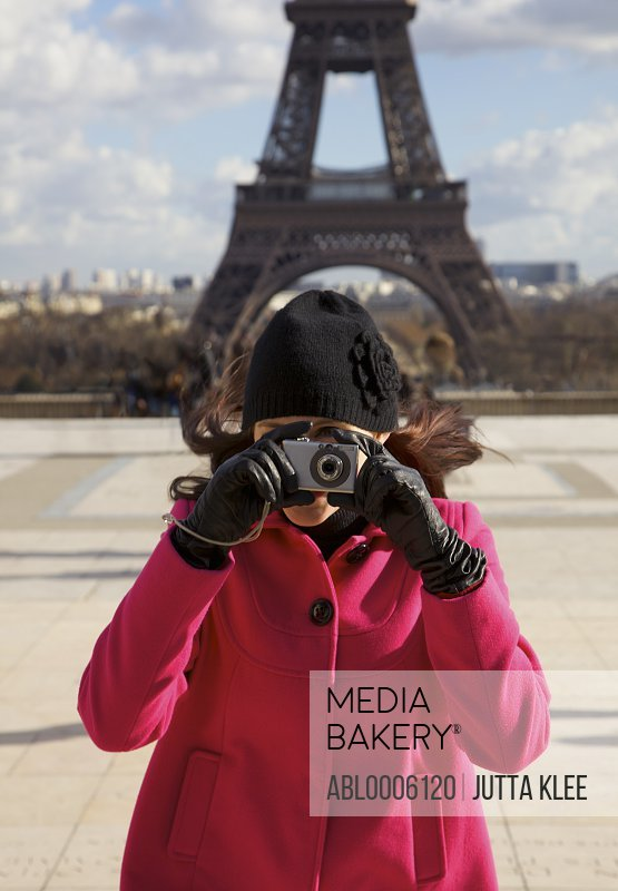 Woman taking a photo in front of the Eiffel Tower