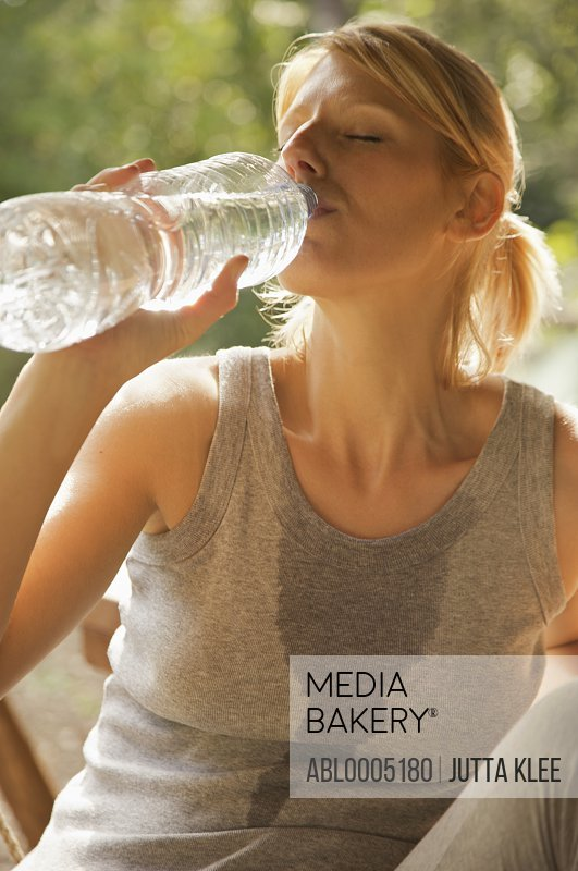 Close up of a young woman drinking water from a bottle with her eyes closed