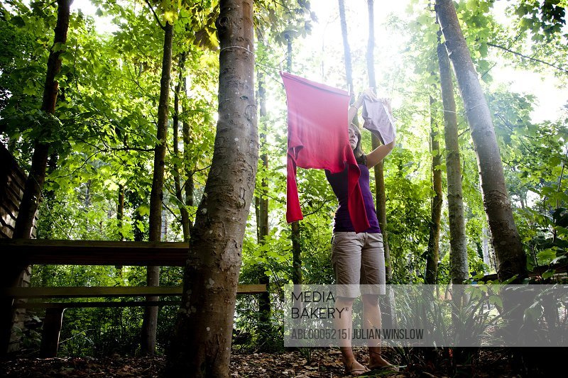 Woman standing in a forest hanging clothes on a clothes line