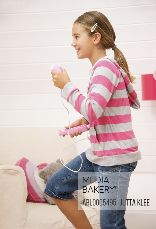 Smiling girl holding a game controller playing and hopping