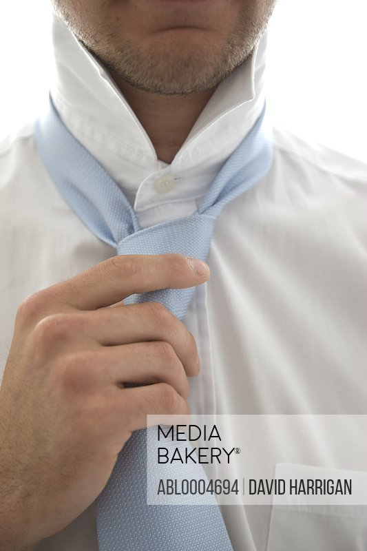 Close up  of a young man tightening his tie