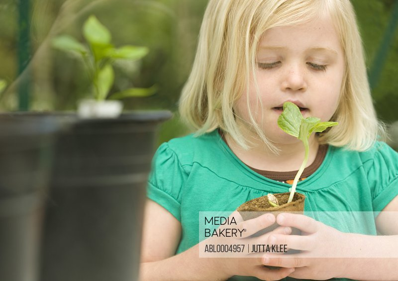 Close up of a Girl inhaling and holding a seedling pot