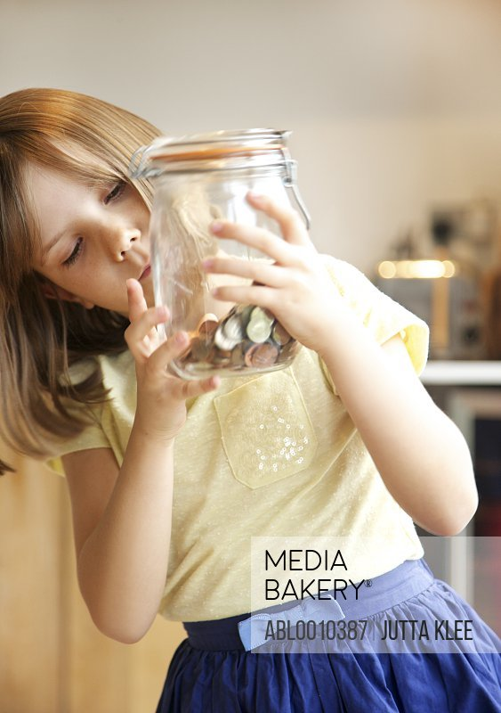 Young Girl Inspecting Jar of Coins