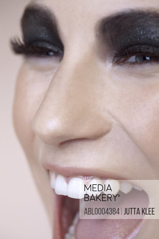 Extreme close up of beautiful young woman with black eyeshadow and mouth open