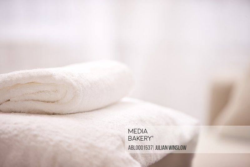Close up of a folded white towel on a massage table