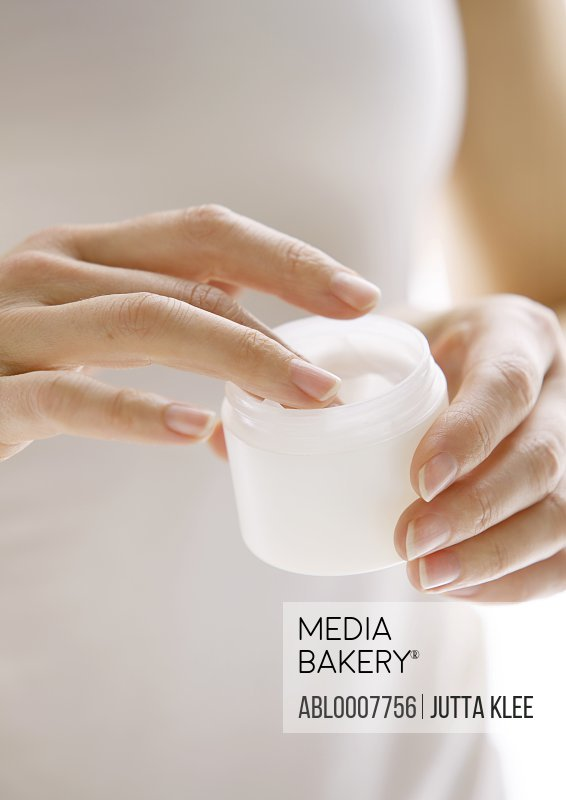 Woman Holding an Open Jar of Cosmetic Cream, Close up view