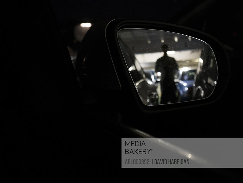 Side View Mirror Reflecting Silhouette aboard Ferry