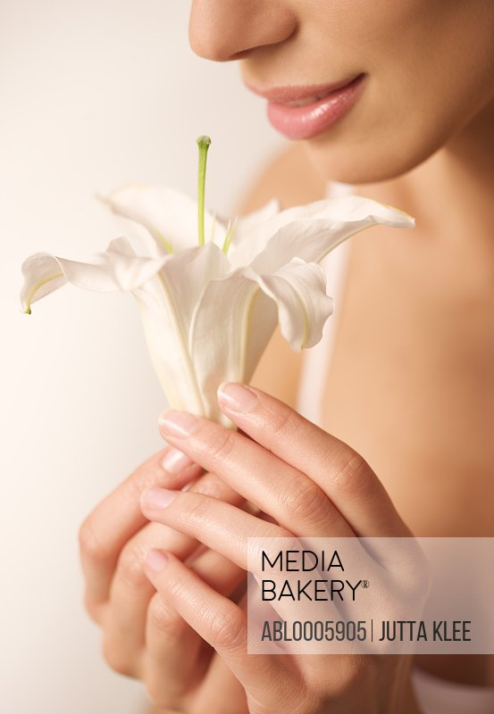 Extreme close up of a woman smelling a white lily