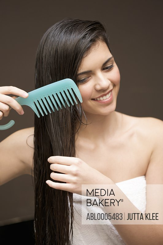 Woman combing her hair with a wide tooth comb