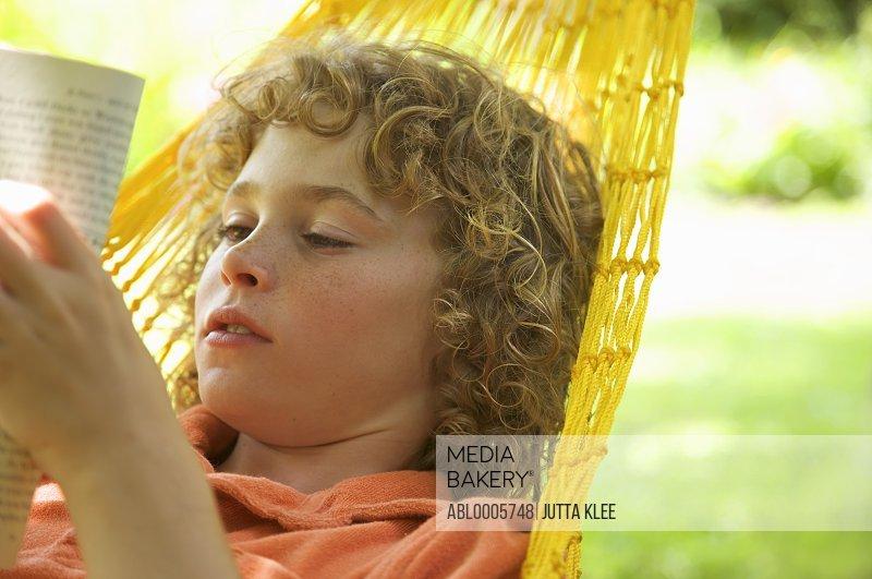 Boy reading on a hammock
