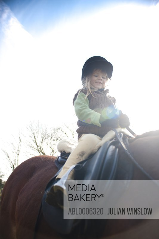 Young girl riding a horse, low angle view