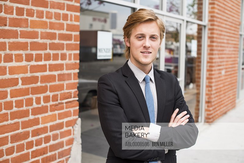 Businessman Standing in front of Office Entrance